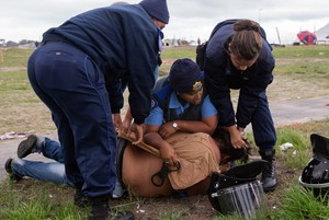 Photo a a woman being detained after protests turn violent in Parkwood.