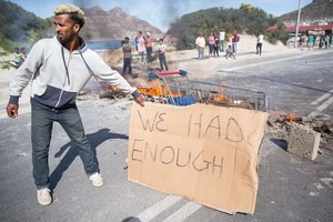 Photo of burning barricade with man holding placard