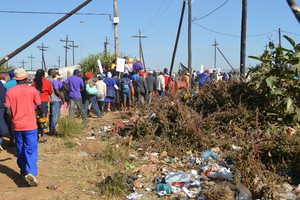 Photo of people marching past rubbish