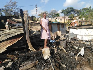 Photo of woman standing on burnt ruins