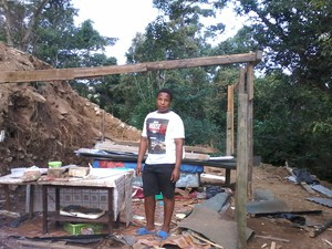 Photo of man in front of his demolished shack