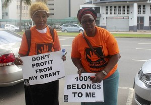 Photo of two protesters against social grant deductions