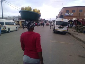 Photo of woman with bucket of oranges on her head