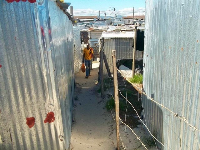 Photo of a man walking between shacks