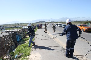 Photo of eskom workers removing illegal connections