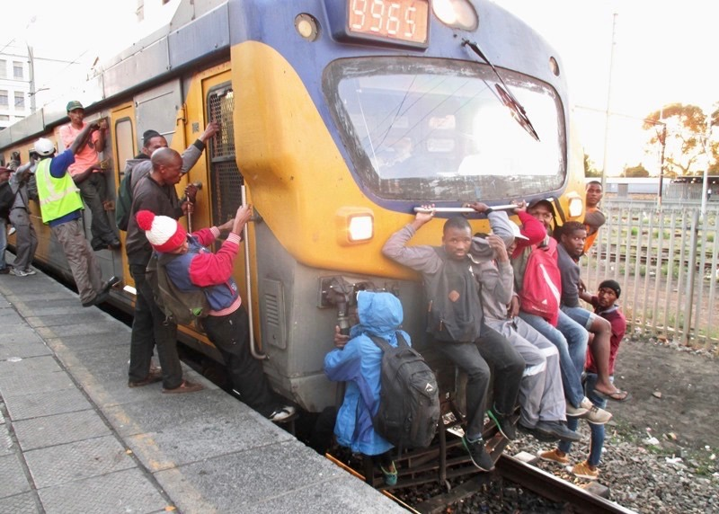 Photo of people hanging onto train